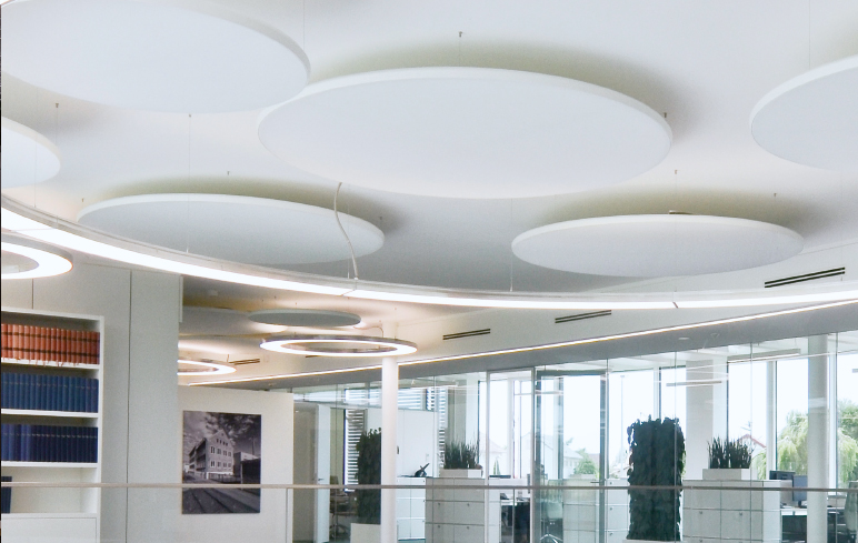 Acoustic Light Panel round, white at the ceiling. With diameters more than 1 m. In Combination with round LED-Pendant luminaires with direct light and a finish of aluminium folished, named ANELLO