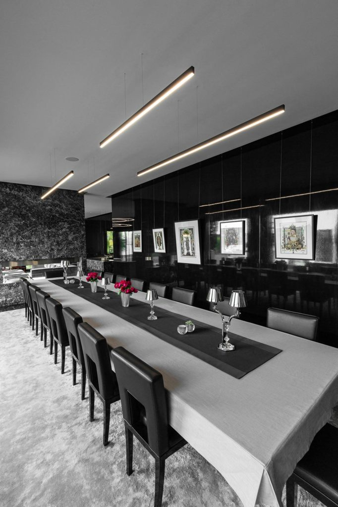A group of four linear pendant lights in black (named Doppio Linea) above a large banquet table in the dining room.