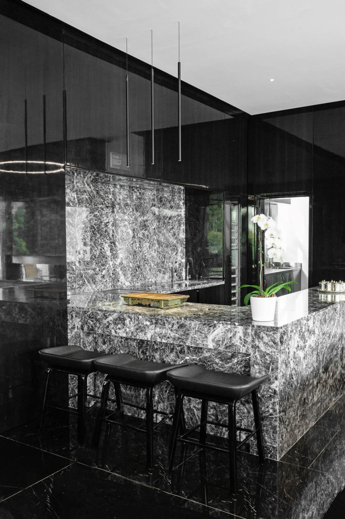 Three small cylindrical pendants (named FINO PENDANT) in black above a kitchen counter.