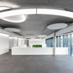 round acoustic elements and pendant luminaires of SATTLER named ANELLO and ACOUSTIC LIGHT PANEL in a modern building